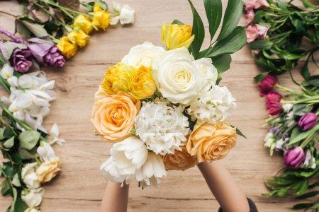 Photo pour Vue partielle du fleuriste tenant un bouquet de fleurs fraîches sur une surface en bois - image libre de droit