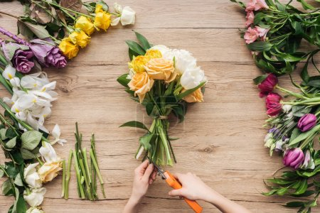 Cropped view of florist cutting flower stalks in bouquet on wooden surface