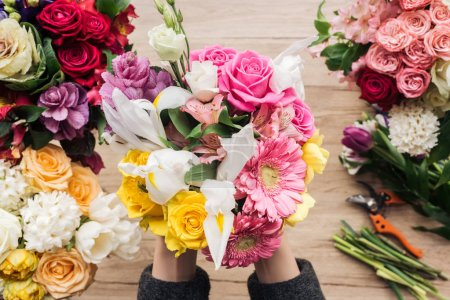Photo for Partial view of florist holding bouquet of fresh flowers on wooden surface - Royalty Free Image