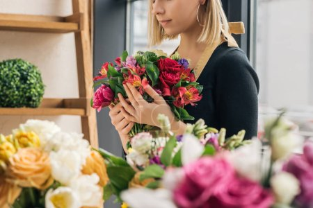 Photo for Cropped view of florist in apron holding bouquet in flower shop - Royalty Free Image