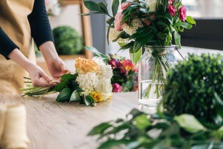 Photo pour Vue partielle de fleuriste faisant bouquet dans la boutique de fleurs - image libre de droit