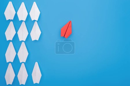Flat lay with white and red paper planes on blue