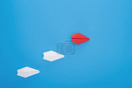 Photo pour Plat poser avec des avions de papier rouge et blanc sur bleu - image libre de droit