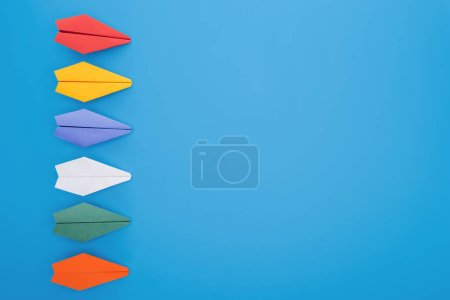 Flat lay with colorful paper planes on blue surface