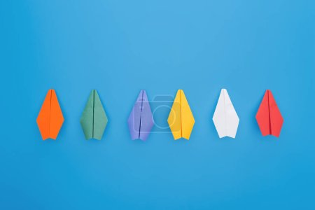Photo for Flat lay with colorful paper planes on blue surface - Royalty Free Image