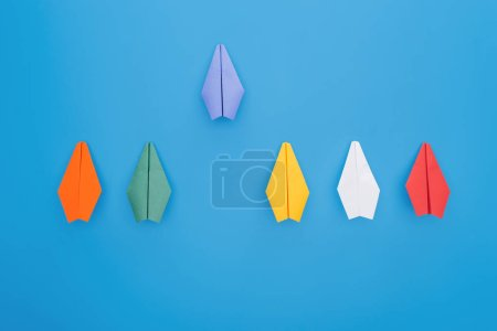 Foto de Plana se pone con aviones de papel de colores en la superficie azul - Imagen libre de derechos