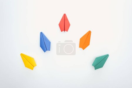 Flat lay with colorful paper planes on white surface