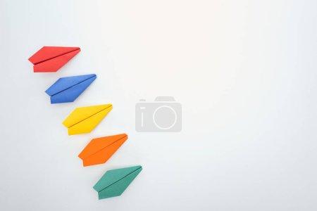 Foto de Plana se pone con aviones de papel de colores sobre la superficie blanca - Imagen libre de derechos