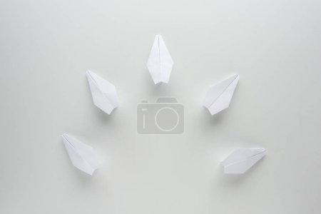 Foto de Lay Flat con aviones de papel blanco sobre la superficie gris - Imagen libre de derechos
