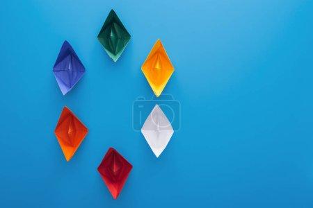 Photo pour Pose plate avec des bateaux en papier coloré sur la surface bleue - image libre de droit