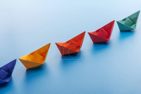 Colorful bright paper boats on light blue surface