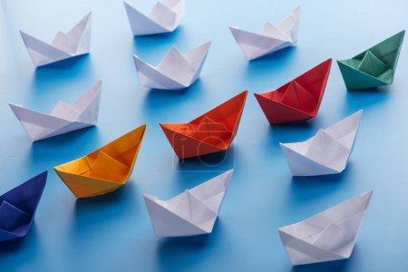 Foto de Barcos de papel de brillantes colores en la superficie azul claro - Imagen libre de derechos