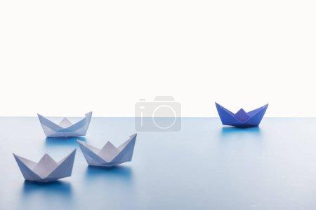 Foto de Barcos de papel sobre la superficie azul claro sobre fondo blanco - Imagen libre de derechos