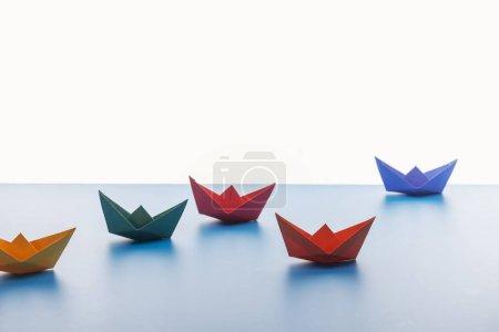 Foto de Barcos de papel de colores en la superficie de luz sobre fondo blanco - Imagen libre de derechos