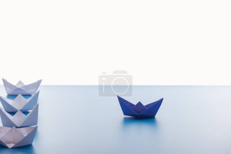 Paper boats on light blue surface on white background
