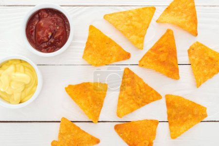 Photo for Top view of tasty nachos and sauces on white wooden table - Royalty Free Image