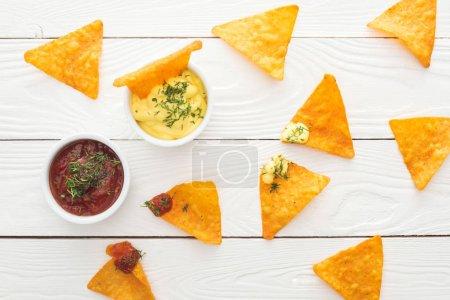 Photo pour Vue de dessus de nachos et sauces savoureuses sur la surface blanche et en bois - image libre de droit