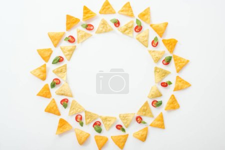 Photo for Top view of tasty nachos and sliced chili peppers with basil on white background with copy space - Royalty Free Image