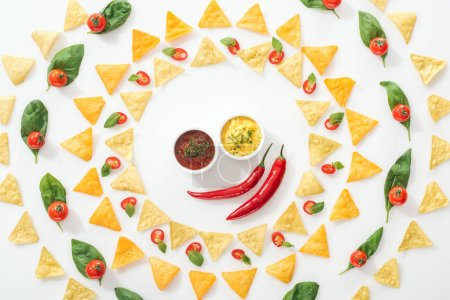 Photo for Top view of tasty nachos, sauces and sliced chili peppers with basil and cherry tomatoes - Royalty Free Image