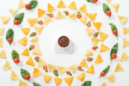 Photo for Top view of tasty nachos, sauce and sliced chili peppers with basil and cherry tomatoes - Royalty Free Image