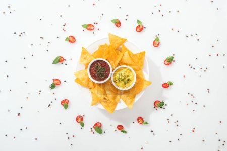 Photo for Top view of tasty nachos and sauces on plate, spices and sliced chili peppers with basil leaves - Royalty Free Image