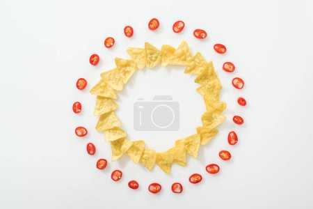 Photo for Top view of sliced chili peppers and tasty nachos on white background with copy space - Royalty Free Image