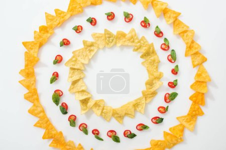 Photo for Top view of sliced chili peppers and tasty nachos with basil leaves on white background - Royalty Free Image