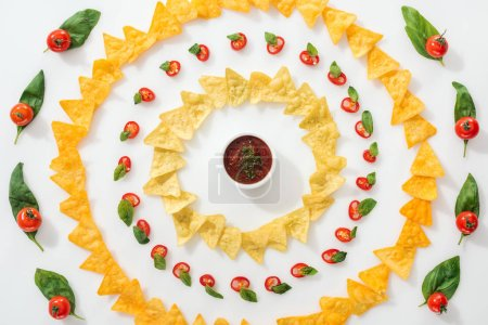 Photo for Top view of sliced chili peppers, sauce and tasty nachos with basil leaves and cherry tomatoes - Royalty Free Image