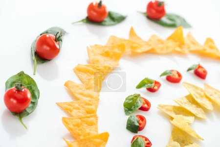 Photo for Selective focus of tasty nachos, cherry tomatoes and chili peppers with basil - Royalty Free Image