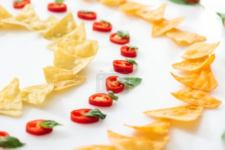 Photo for Selective focus of tasty nachos and chili peppers with basil on white background - Royalty Free Image