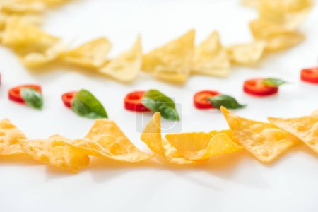 selective focus of tasty nachos and chili peppers with basil on white background