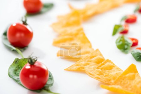 Photo for Selective focus of tasty nachos and cherry tomatoes with basil on white background - Royalty Free Image