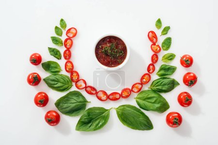 flat lay with cut chili peppers, basil leaves, sauce and ripe cherry tomatoes on white background