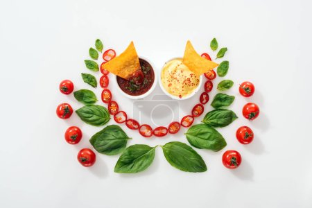 Photo for Top view of cut chili peppers, basil leaves, nachos in sauces and ripe cherry tomatoes - Royalty Free Image