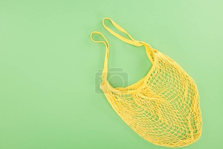 Photo for Top view of yellow string bag on light green background - Royalty Free Image