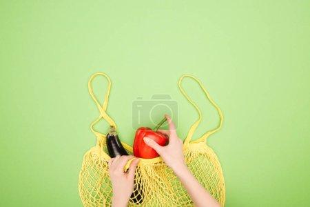 Photo pour Vue recadrée des mains femelles, poivron rouge et aubergine dans le sac de ficelle jaune sur le fond vert clair - image libre de droit
