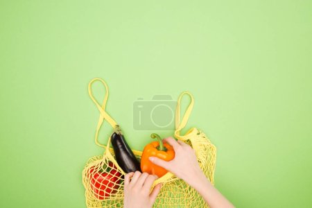 Foto de Vista parcial de la mujer tomando el pimiento fresco de la bolsa de cuerda amarilla con verduras enteras en la superficie verde claro - Imagen libre de derechos