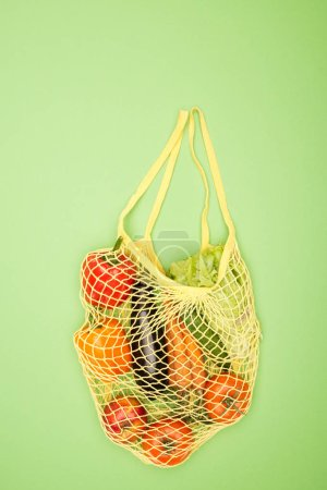 Photo for Top view of yellow string bag with ripe organic vegetables on light green surface with copy space - Royalty Free Image