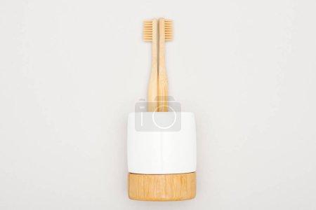 Photo pour Brosses à dents en bambou en stand sur fond gris - image libre de droit