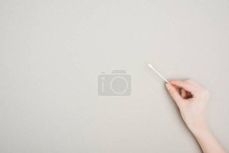 Foto de Cropped view of woman holding cotton swab on grey background - Imagen libre de derechos