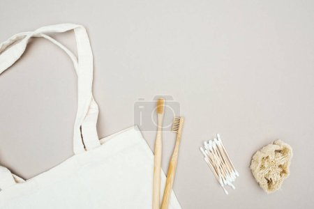 Photo for Wooden toothbrushes, organic loofah, cotton swabs and white cotton bag on grey background - Royalty Free Image