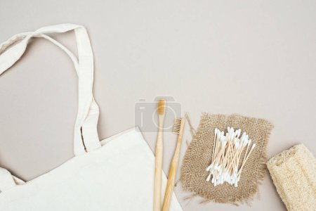 Photo for Wooden toothbrushes, organic loofah, cotton swabs, sackcloth and white cotton bag on grey background - Royalty Free Image