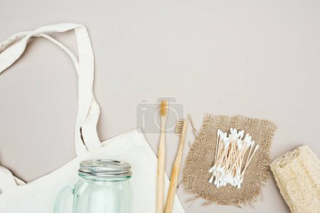 Photo for Wooden toothbrushes, organic loofah, cotton swabs, sackcloth, glass jar and white cotton bag - Royalty Free Image