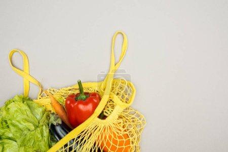 Photo pour Sac à ficelle jaune avec légumes frais mûrs sur fond gris - image libre de droit
