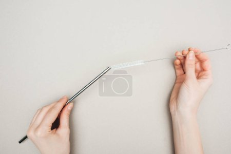 Photo for Partial view of woman holding cleaning brush and stainless steel straw on grey - Royalty Free Image