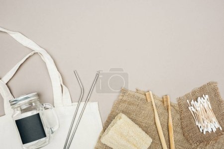 Photo for Bamboo toothbrushes, organic loofah, cotton swabs, brown sackcloth, cotton bag with jar and stainless steel straws on grey background - Royalty Free Image