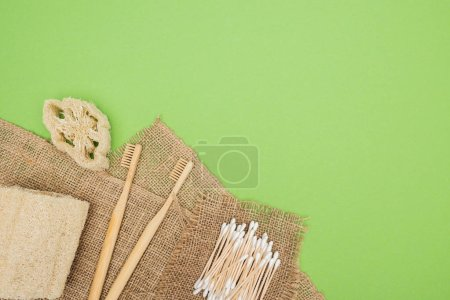 Photo for Bamboo toothbrushes, organic loofah, cotton swabs and brown sackcloth on light green background - Royalty Free Image