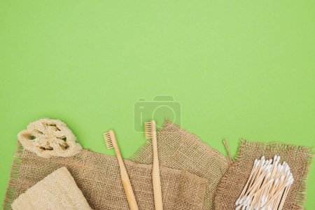 Photo for Bamboo toothbrushes, organic loofah, cotton swabs and sackcloth on light green background - Royalty Free Image