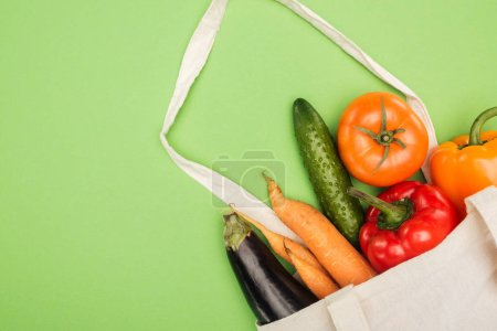 Photo for Cotton bag with fresh ripe vegetables on light green background - Royalty Free Image