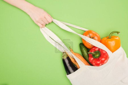 Photo for Partial view of woman holding handle of cotton bag full of ripe vegetables - Royalty Free Image